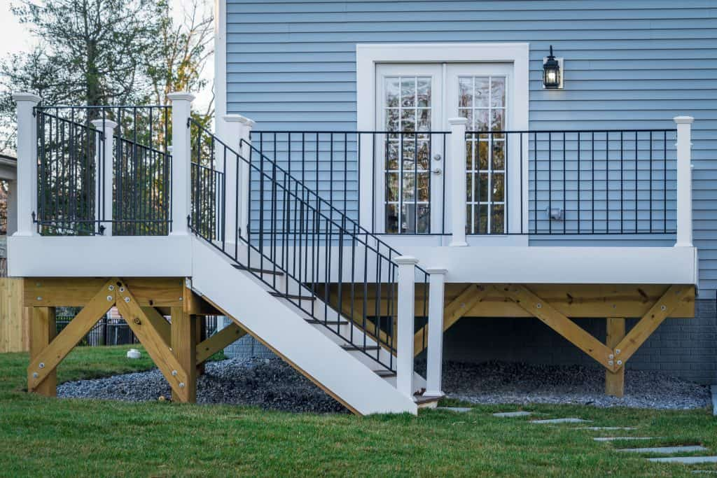 View of a classic backyard wooden deck with black metal balustrades railing and white columns on an American single family home